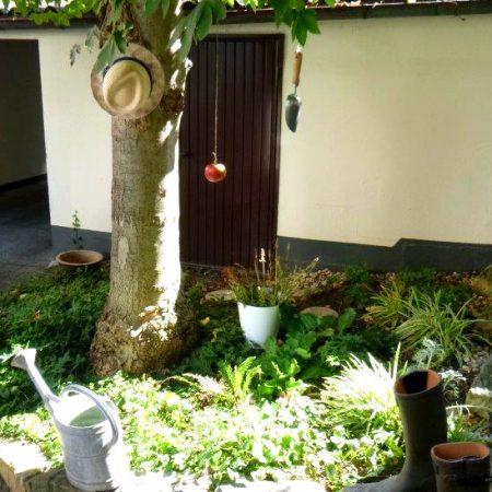 Hinterhof mit einem Baum, Strohhut, Gießkanne und Gummistiefeln